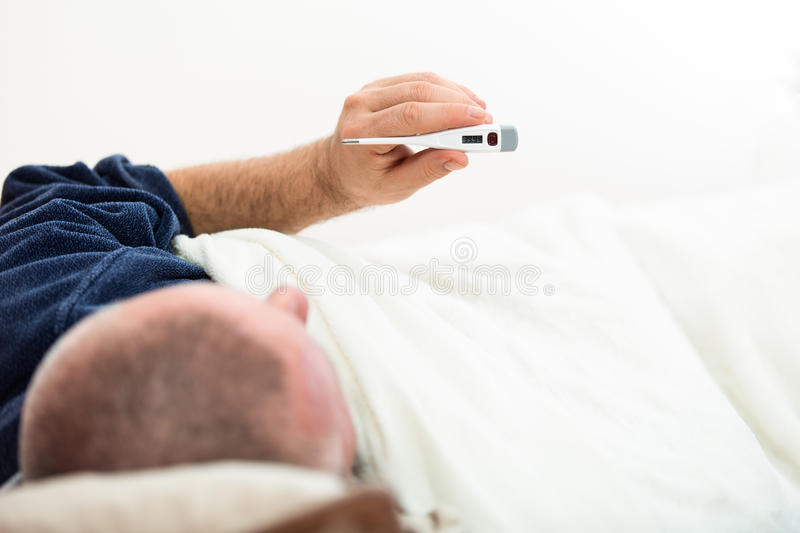 Dramatic image of a sick man laying in bed with fever.  royalty free stock images