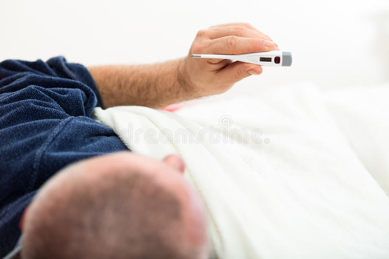 Dramatic image of a sick man laying in bed with fever.  royalty free stock image