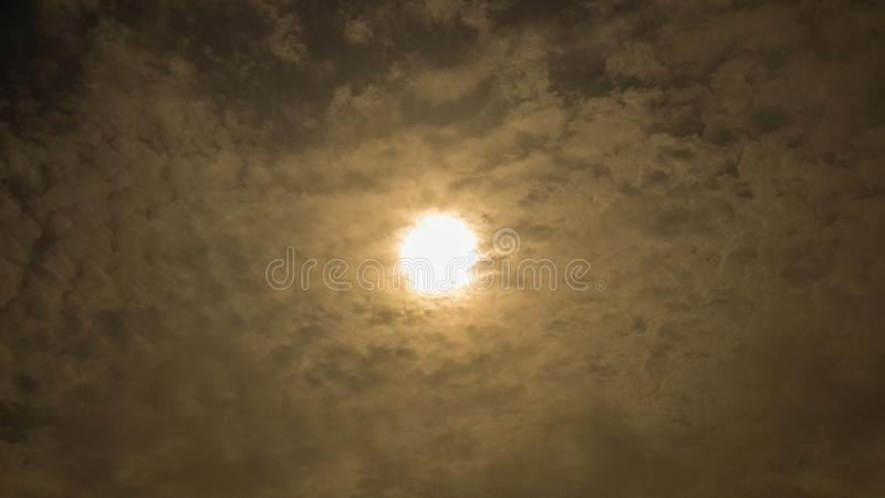 Dramatic impressive and beautiful background, texture. Sun bright behind soft clouds. Dark sky with bright sun clouds in the morni royalty free stock photo