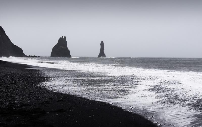 Dramatic landscape of Black Sand Reynisfjara beach in Iceland. On a cloudy day, lanscape, sunset, scenic, icelandic, tourist, vik, stunning, nobody, sky stock photography