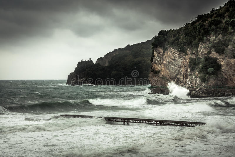 Dramatic landscape with cliffs on sea shore during storm with big stormy waves and dramatic sky with rain in fall season on sea co. Dramatic sea landscape with stock photo