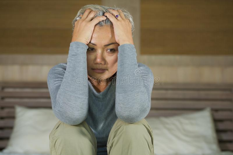 Dramatic lifestyle home portrait of attractive sad and lost middle aged woman with grey hair sitting on bed feeling frustrated. Depressed 40s - 50s mature female stock photography
