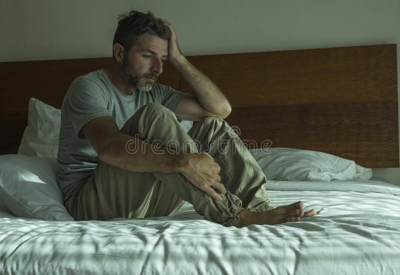 Dramatic lifestyle portrait of man sitting depressed on bed crying desperate feeling sad suffering anxiety crisis and depression royalty free stock images