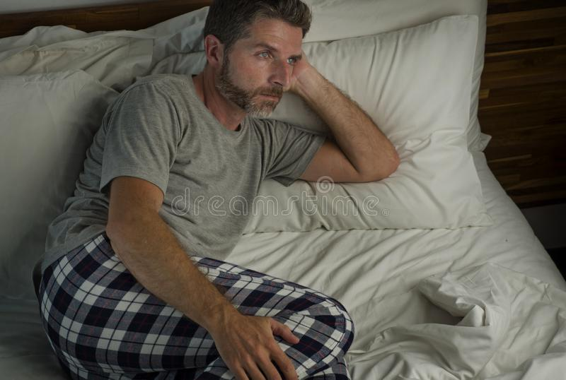 Dramatic lifestyle portrait of young attractive sad and depressed man sitting on bed at night feeling stressed and desperate royalty free stock image