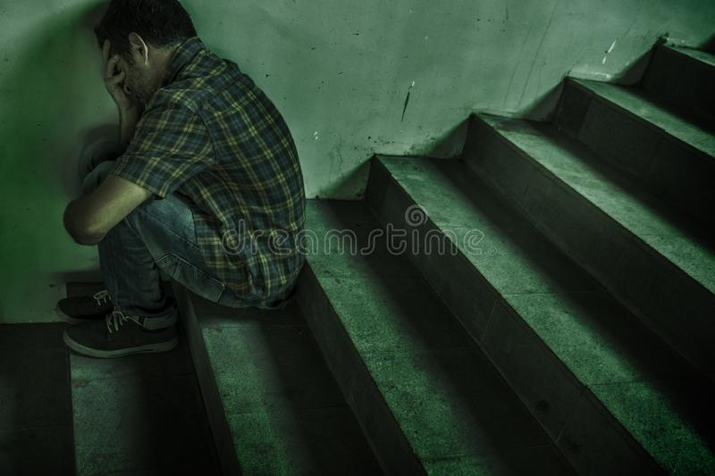 Dramatic lifestyle portrait of young depressed and sad man sitting outdoors on dark street staircase suffering depression problem stock photo