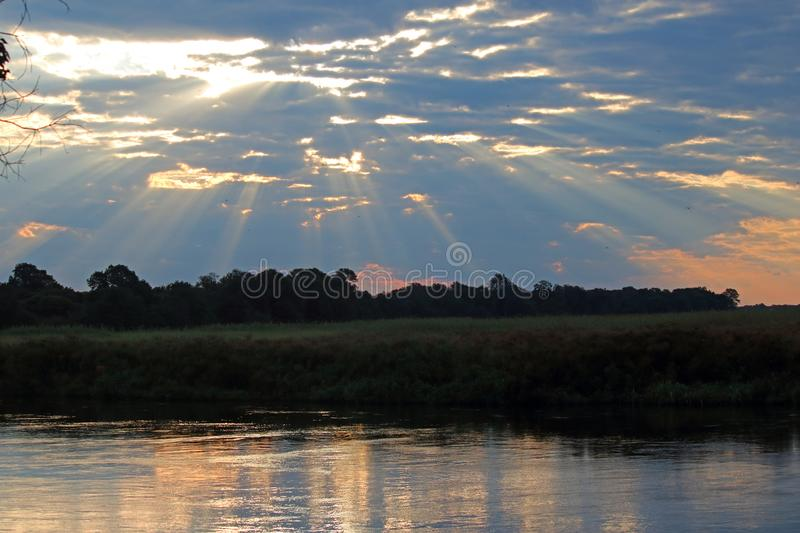 DRAMATIC LIGHT AND CLOUD SCENE OVER THE KAVANGO RIVER. View of sun displaying rays of light from behind broken clouds in the afternoon in Africa in summer with stock photo