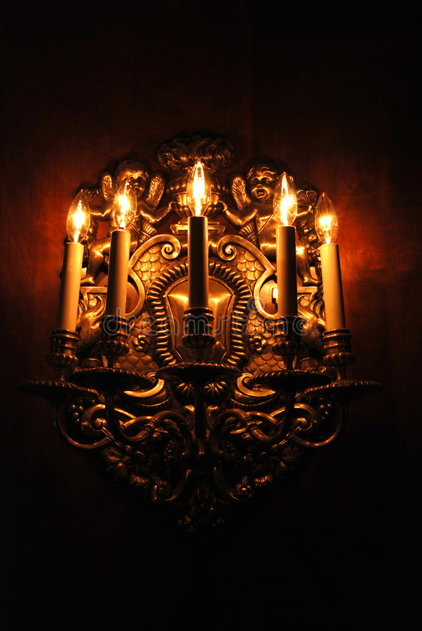 Dramatic Light Fixture. A dramatic gold antique electric light fixture stock photography
