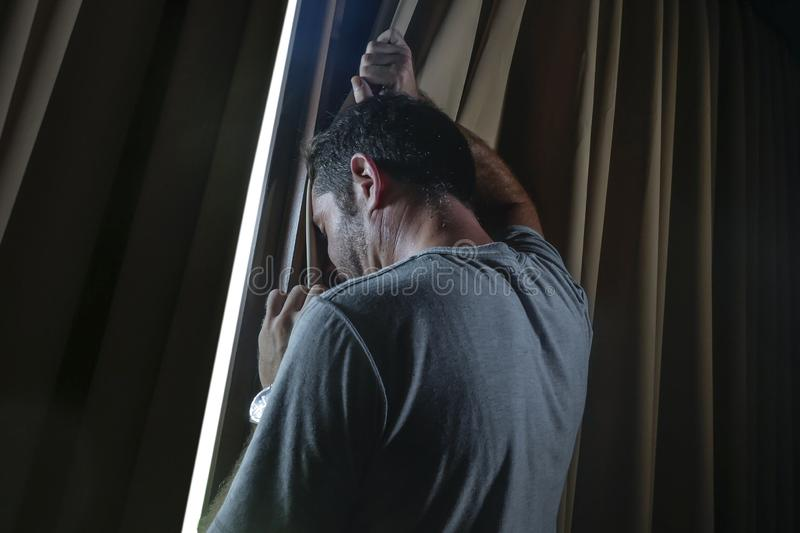 Dramatic light portrait of young sad and depressed attractive man at home looking through room window thoughtful and pensive lost stock images