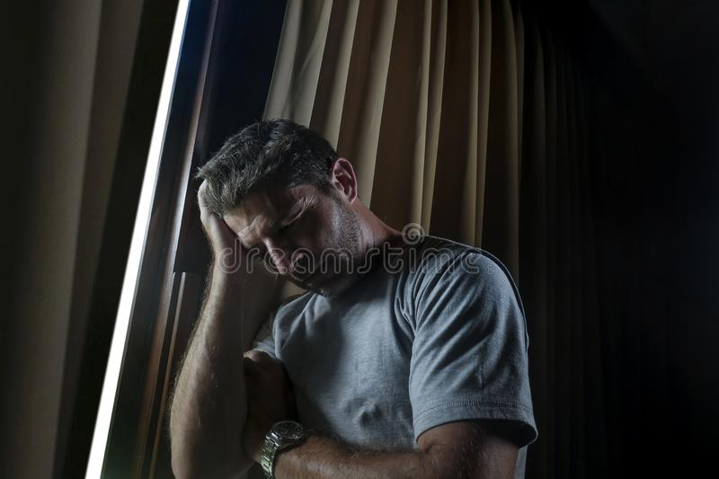 Dramatic light indoors portrait of young sad and depressed attractive man looking through home room window thoughtful and pensive stock photo