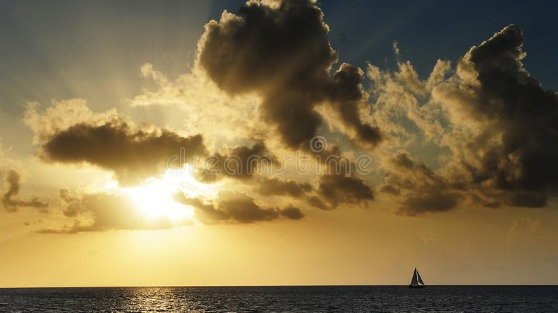 Dramatic light piercing through the clouds and hitting the sea. And sailing boat.Amazing Greece stock photo