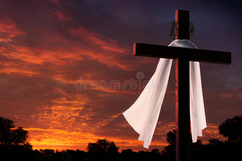 Dramatic Lighting on Christian Easter Morning Cross At Sunrise. This dramatic sunrise lighting with large cross, burial cloth and crown of thorns makes a great stock images