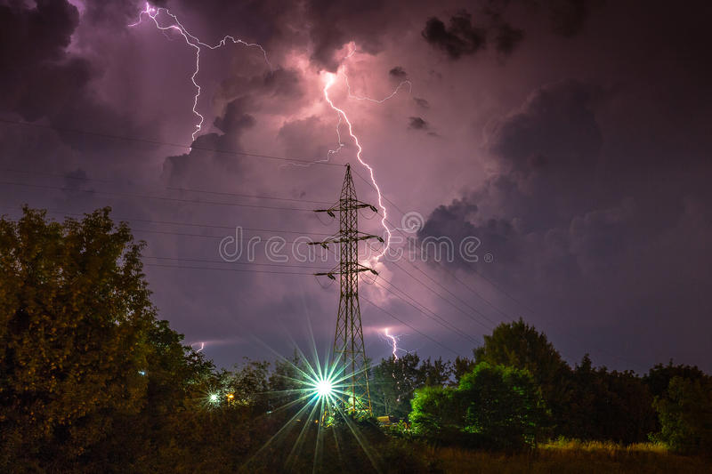 Dramatic lightning over high voltage pylon royalty free stock photo