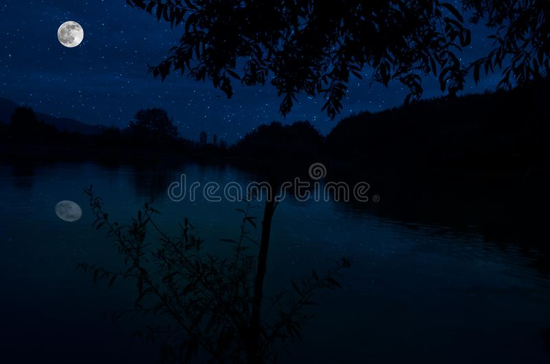 This dramatic moon rise in a deep blue night time sky is accented by highlighted clouds and beautiful, calm lake reflection. royalty free stock image