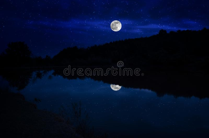 This dramatic moon rise in a deep blue night time sky is accented by highlighted clouds and beautiful, calm lake reflection. royalty free stock photography
