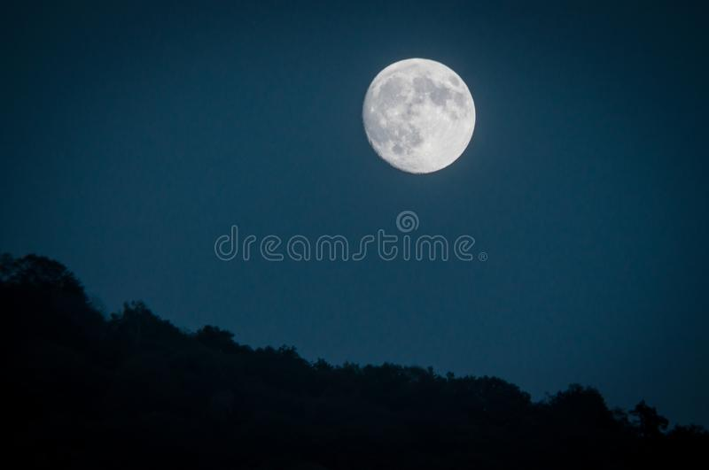 Dramatic mountain moon rise with deep blue night time sky and layered hills in the distance stock photo