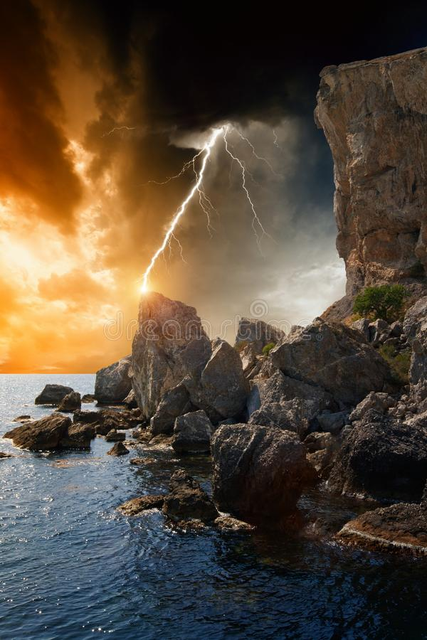 Dramatic nature background. Rocks, sea, dark sky with lightning royalty free stock images