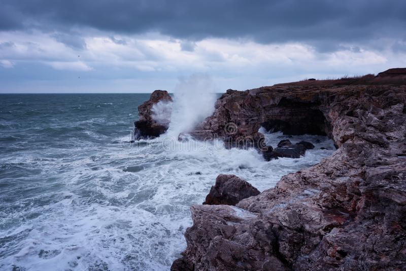 Dramatic nature background - big waves and dark rock in stormy sea, stormy weather. Dramatic scene. Contrasting colors.Beautiful natural landscape, seascape at stock photography