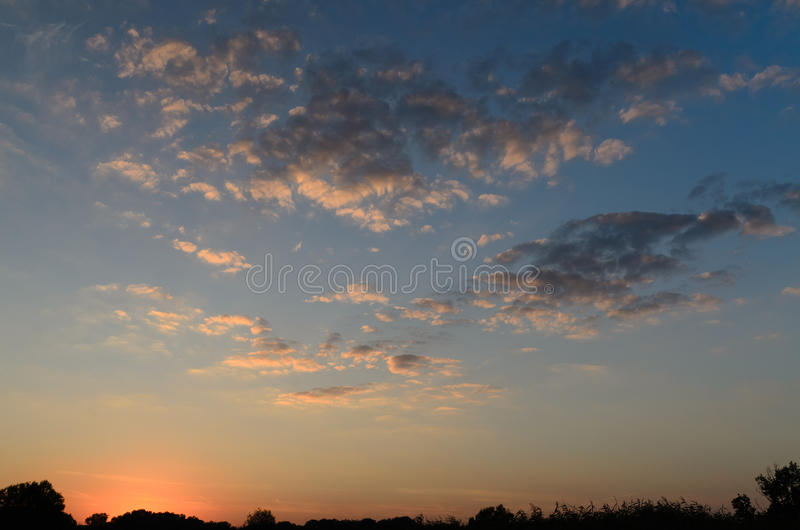 Dramatic nature image with horizon line at sunset. Dramatic scenic nature image with horizon line under a cloudy sky at sunset royalty free stock image