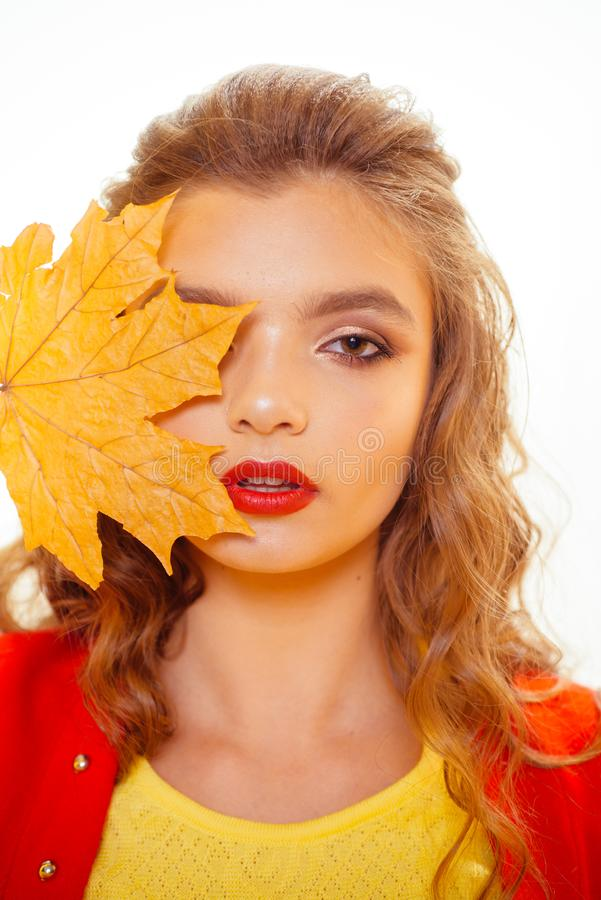 The dramatic nature of the red lipstick. Pretty girl cover face with autumn leaf. Fashion model with decorative fall stock image