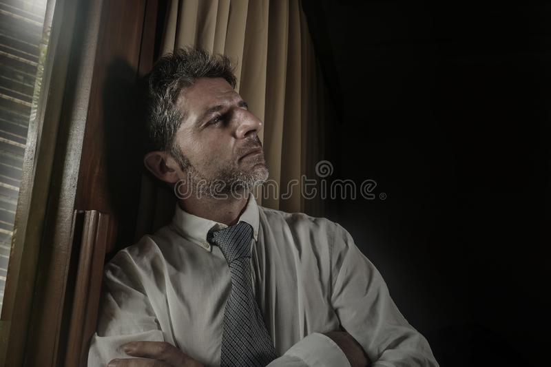 Dramatic night light office portrait of business man working late leaning worried and frustrated on window thoughtful and pensive stock image