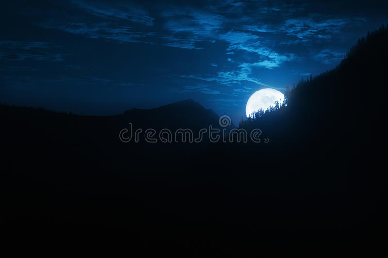Dramatic Nighttime Moonrise Over Mountain Ridge and Pine Trees. This is a photo llustration of an instensely bright sunrise over a Pine Forest ridge in the Rocky stock photos