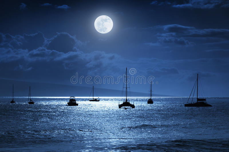 Dramatic Nighttime Ocean Scene With Beautiful Full Blue Moon in Lahaina on the island of Maui, Hawaii. This dramatic photo illustration of a nighttime sky over a stock photography
