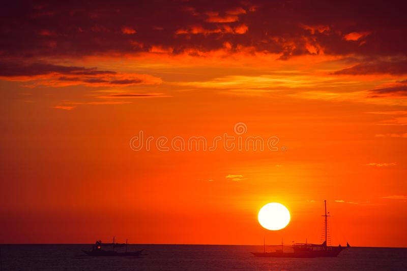 Dramatic orange sea sunset with boats. Summer time. Travel to Philippines. Luxury tropical vacation. Boracay paradise island. stock photo