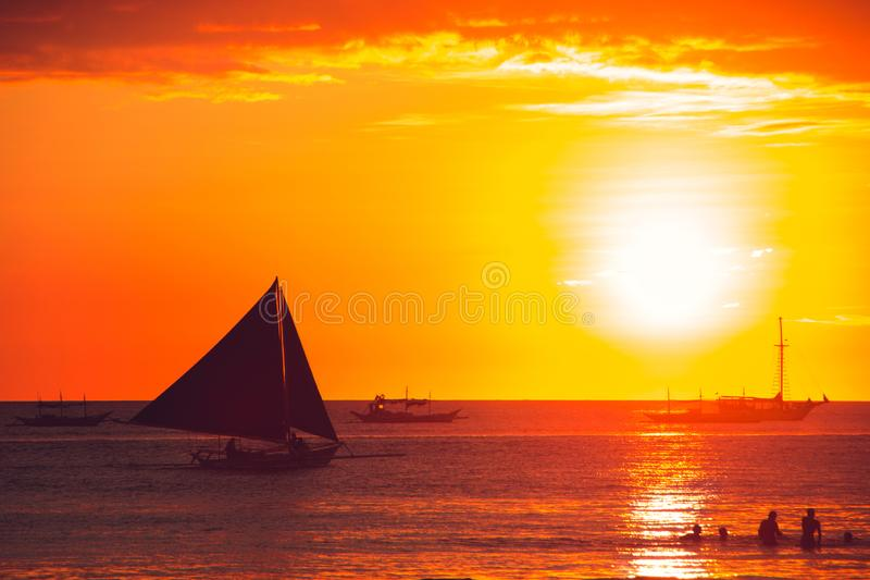 Dramatic orange sea sunset with sailboat. Summer time. Travel to Philippines. Luxury tropical vacation. Boracay paradise island. Nature background. Seascape royalty free stock image