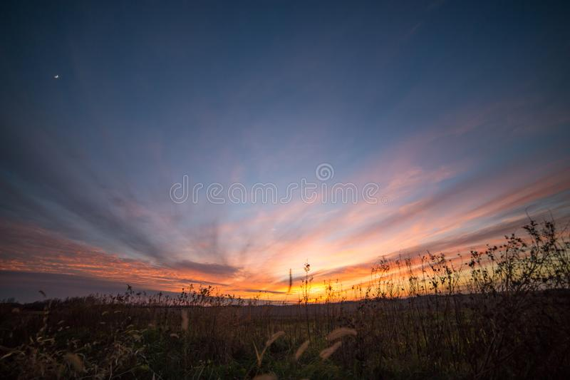 Dramatic Partially Cloudy Crimson Sunset Sky with Moon Crescent royalty free stock photos