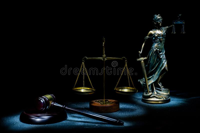 Dramatic photo with light brush statuettes of Themis, scales and judge`s hammer on a stone background stock photo