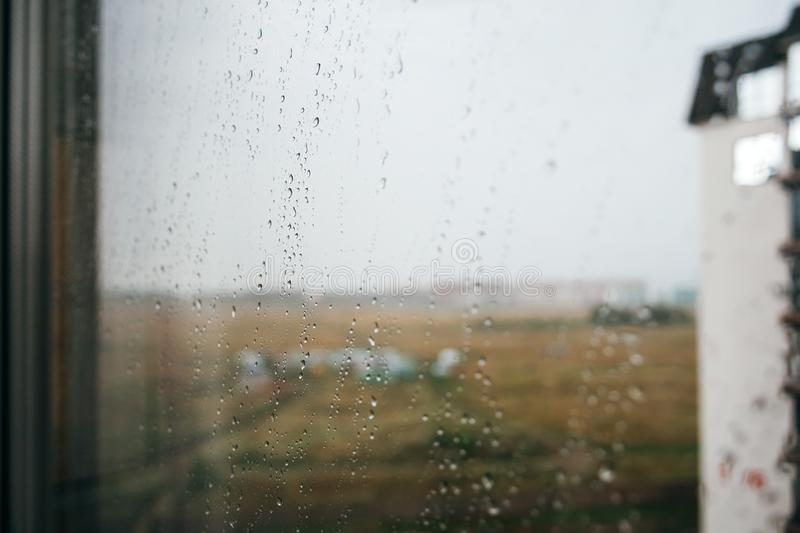 Dramatic photo during rain: blurred view through a glass window with drops of water. Autumn, depressive, rainy weather stock photos