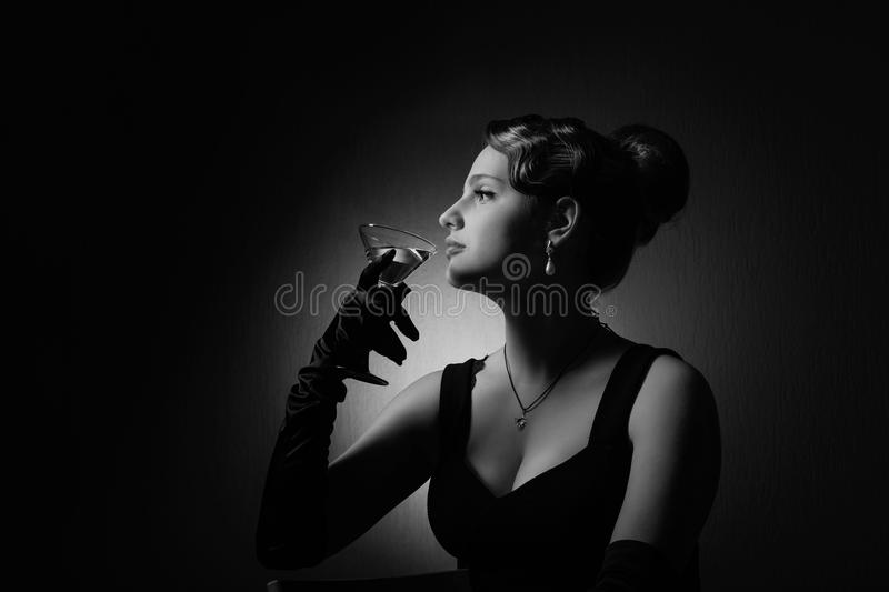 Dramatic portrait of a beautiful woman with glass of martini . Dramatic portrait of a beautiful woman in black dress with perfect hair and makeup .Girl with stock photo