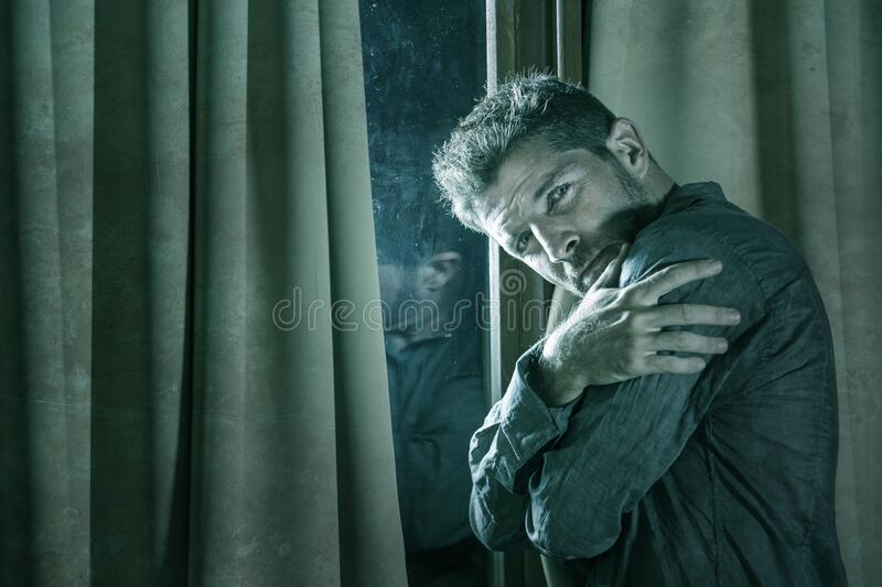 Dramatic portrait of depressed and sick man suffering from psychosis illness or mental disorder looking weird and helpless in stock photo