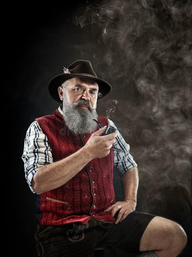 Dramatic portrait of senior smoking tobacco pipe. Dramatic portrait of gray bearded senior man in hat smoking tobacco pipe. view of Austrian, Tyrolean, Bavarian royalty free stock photography
