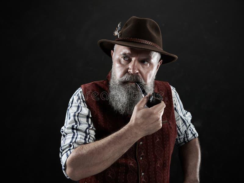 Dramatic portrait of senior smoking tobacco pipe. Dramatic portrait of gray bearded senior man in hat smoking tobacco pipe. view of Austrian, Tyrolean, Bavarian royalty free stock photo