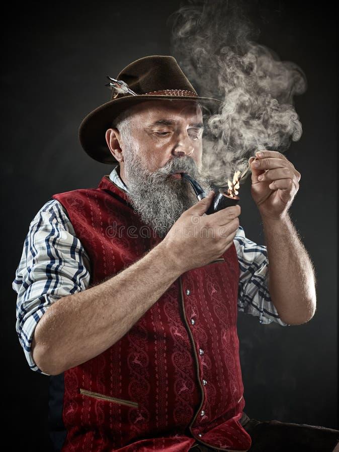 Dramatic portrait of senior smoking tobacco pipe. Dramatic portrait of gray bearded senior man in hat smoking tobacco pipe. view of Austrian, Tyrolean, Bavarian stock photography