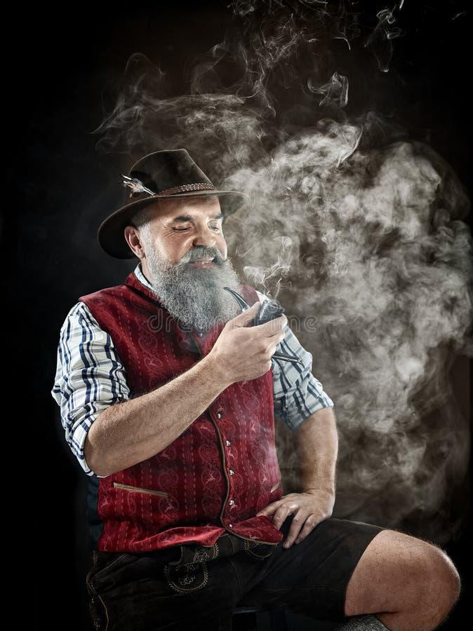 Dramatic portrait of senior smoking tobacco pipe. Dramatic portrait of gray bearded senior man in hat smoking tobacco pipe. view of Austrian, Tyrolean, Bavarian stock photo