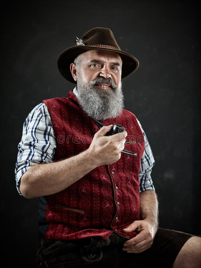 Dramatic portrait of senior smoking tobacco pipe. Dramatic portrait of gray bearded senior man in hat smoking tobacco pipe. view of Austrian, Tyrolean, Bavarian stock image