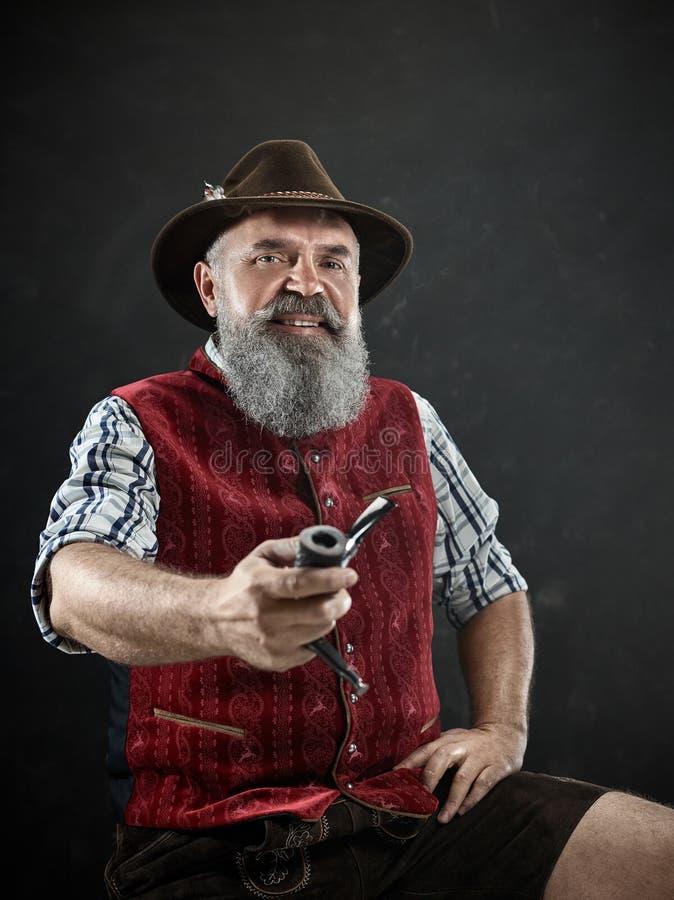 Dramatic portrait of senior smoking tobacco pipe. Dramatic portrait of gray bearded smiling senior man in hat smoking tobacco pipe. view of Austrian, Tyrolean stock photo