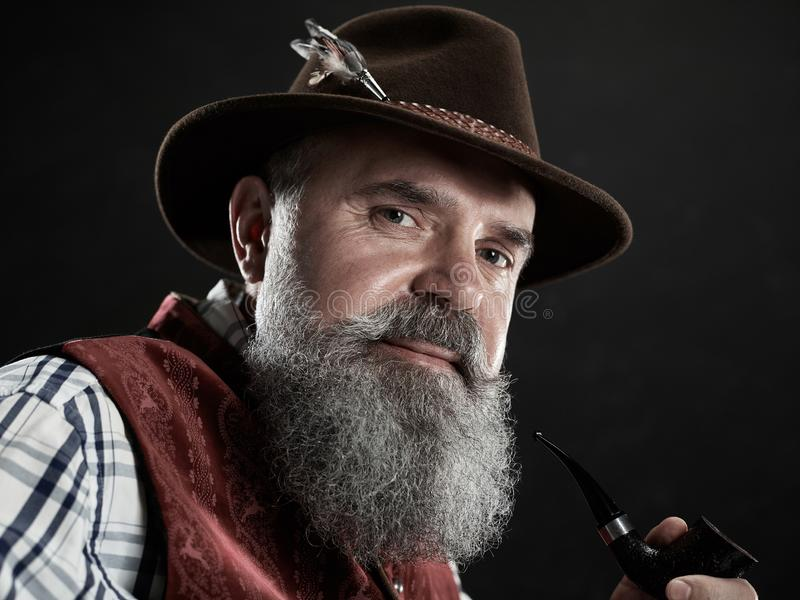 Dramatic portrait of senior smoking tobacco pipe. Dramatic portrait of gray bearded smiling senior man in hat smoking tobacco pipe. view of Austrian, Tyrolean stock image