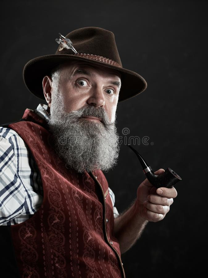 Dramatic portrait of senior smoking tobacco pipe. Dramatic portrait of gray bearded surprised senior man in hat smoking tobacco pipe. view of Austrian, Tyrolean stock image