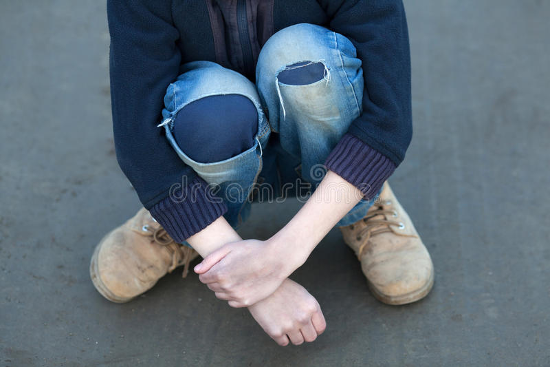Dramatic portrait of a little homeless boy. Poverty, city, street, torn pants, dirty hand stock photography