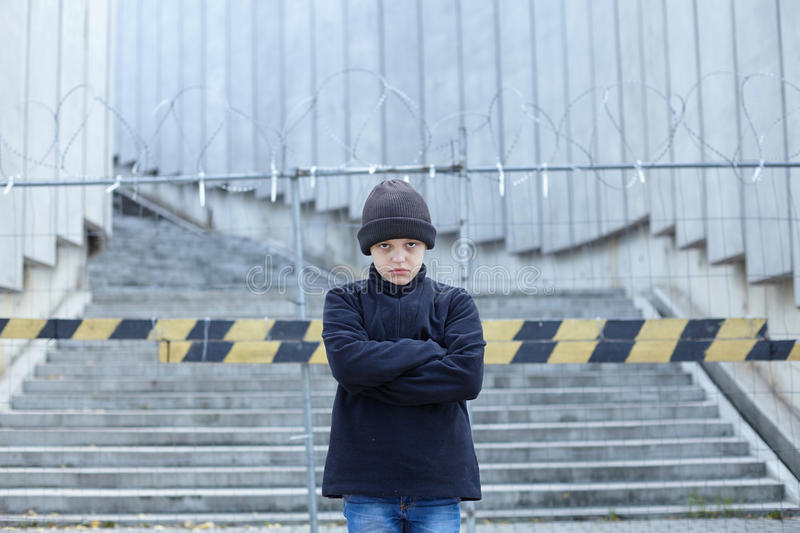 Dramatic portrait of a little homeless boy on the street. Poverty, city stock photos