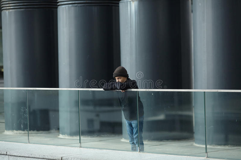 Dramatic portrait of a little homeless boy on the street. Poverty, city stock image