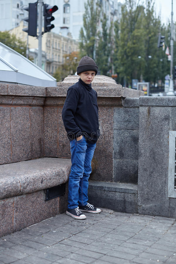 Dramatic portrait of a little homeless boy on the street. Poverty, city royalty free stock photos