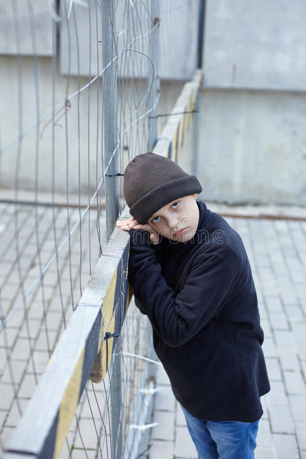 Dramatic portrait of a little homeless boy on the street. Poverty, city royalty free stock image