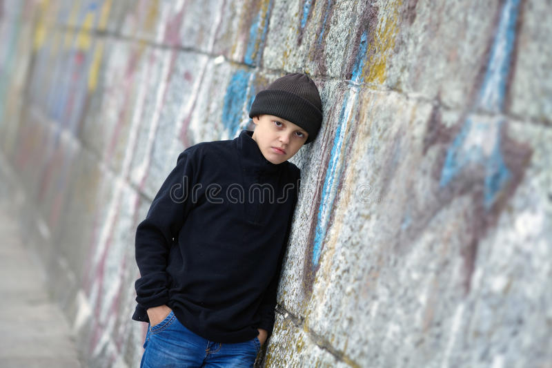Dramatic portrait of a little homeless boy on the street. Poverty, city royalty free stock photography