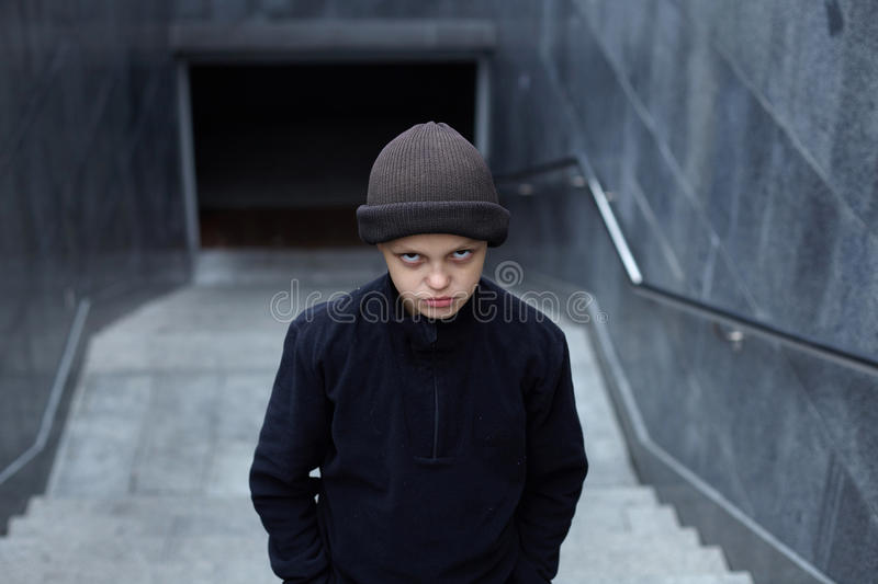 Dramatic portrait of a little homeless boy on the street. Poverty, city royalty free stock photo