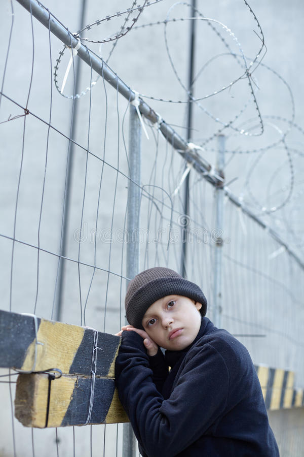 Dramatic portrait of a little homeless boy on the street. Poverty, city stock images