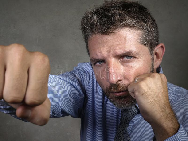 Dramatic portrait of middle aged upset and fierce businessman boxing throwing punch looking furious suffering work stress fighting stock photos